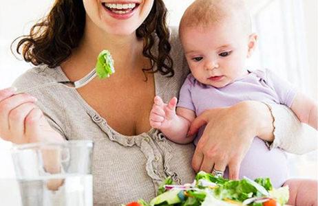 Мамочка с малышом на руках ест салат