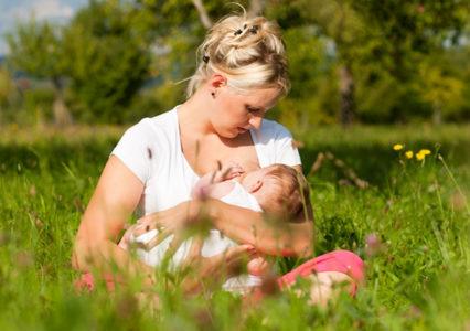 Молодая мамочка кормит ребенка на природе