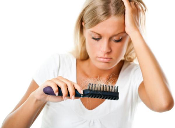 Девушка смотрит на щетку для волос