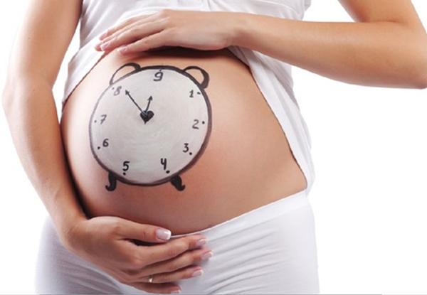 Беременная с нарисованными на животе часами