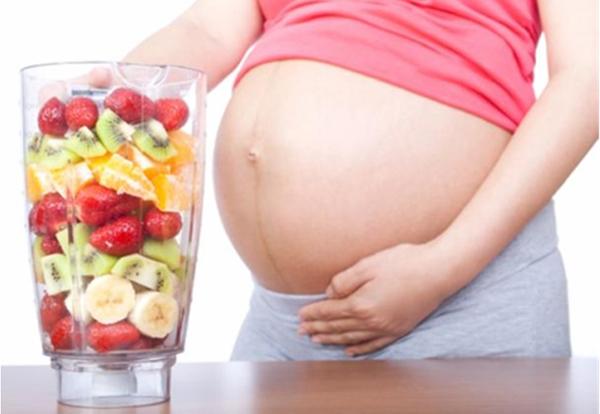 Беременная с огромным стаканов фруктов