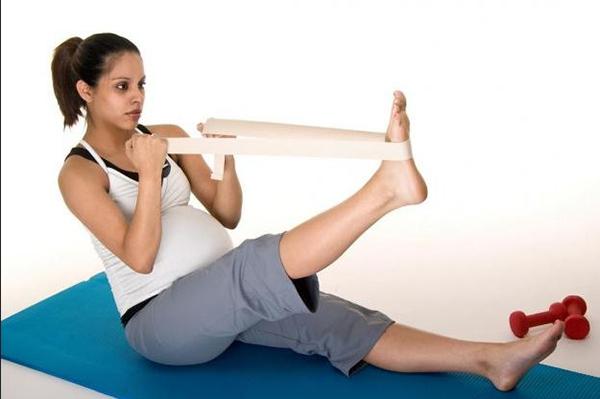 Беременная занимается упражнениями
