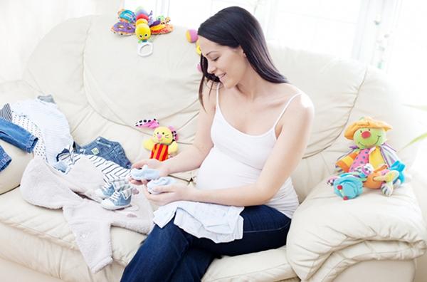 Беременная с вещами для младенца