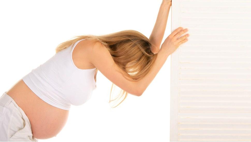 Беременная держится за стену