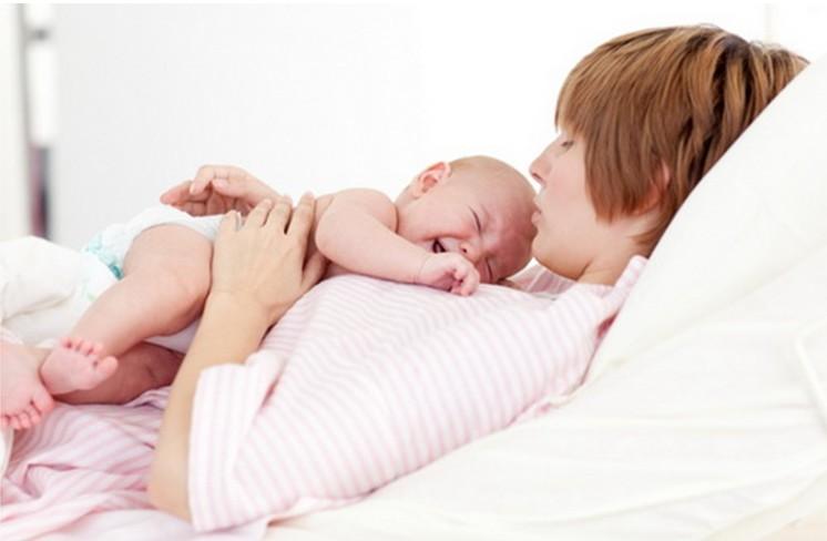 Женщина держит плачущего младенца