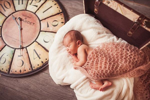 Спящий возле часов младенец
