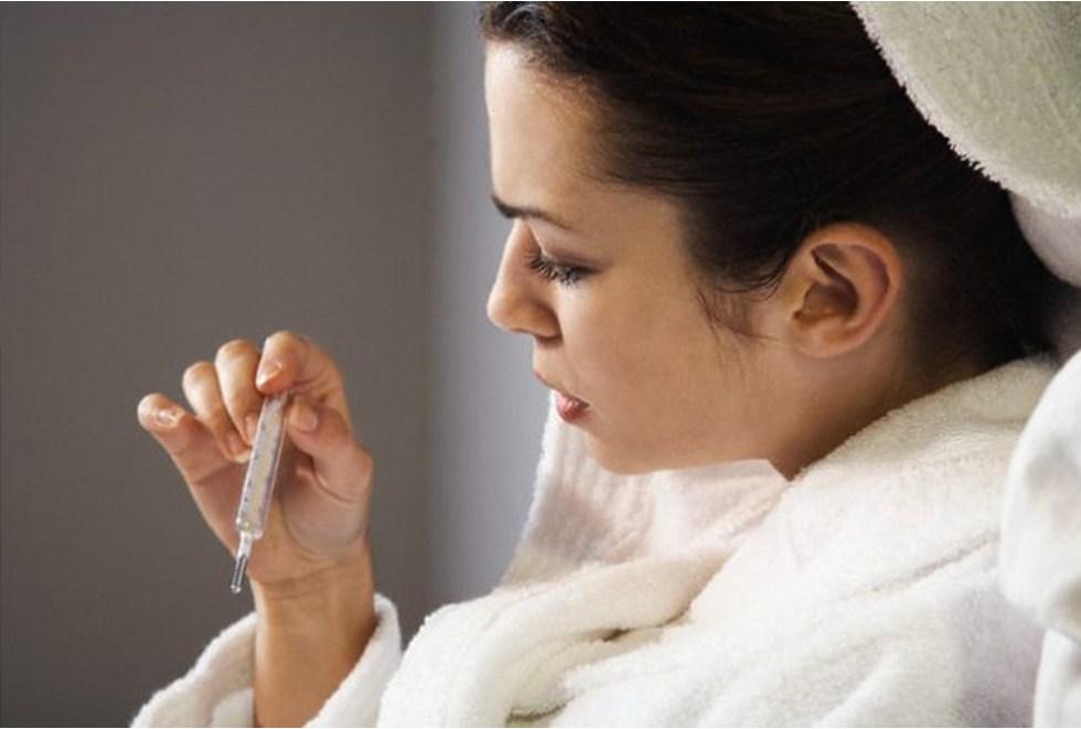 Женщина в халате смотрит на термометр