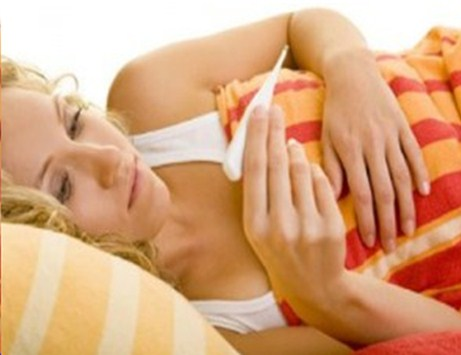 Лежащая женщина смотрит на термометр