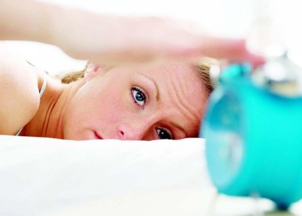 Проснувшаяся женщина смотрит на будильник