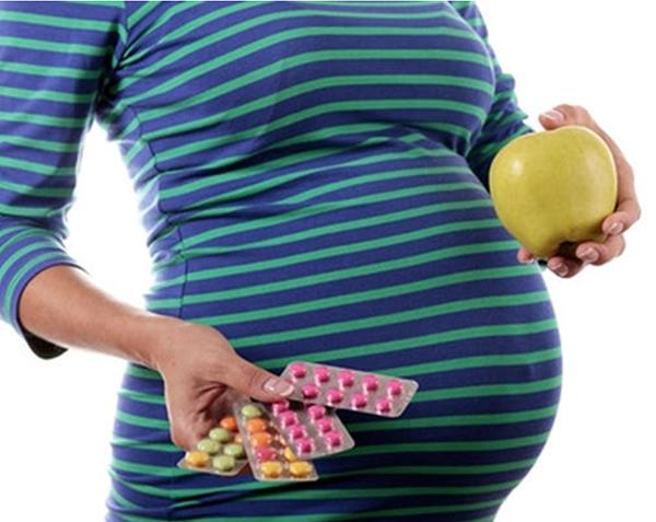 Беременная с яблоком и таблетками