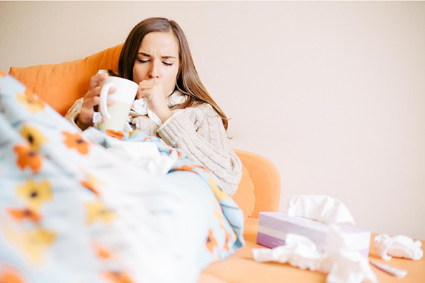 Беременная с чашкой под одеялом