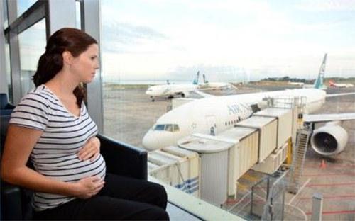 Беременная стоит у окна аэропорта