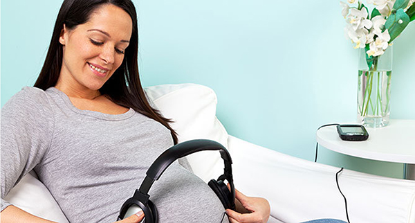 Беременная надевает наушники на животик