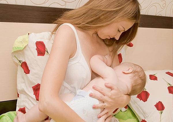 Молодая мама кормит малыша