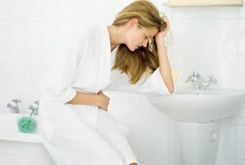 Девушка в ванной держится за живот