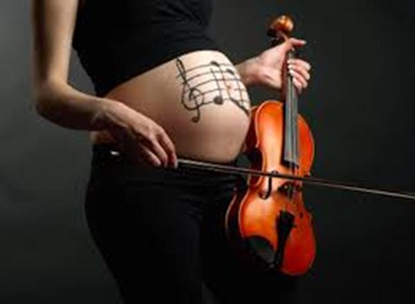 Беременная играет животику на скрипке