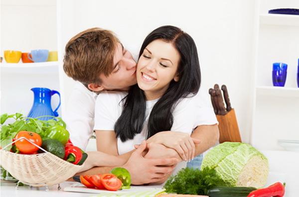 Пара обнимается за столом с продуктами