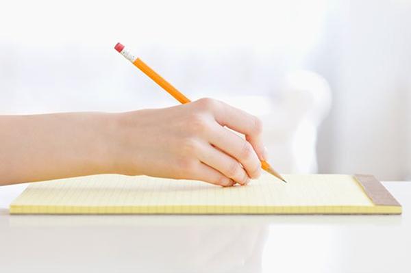 Рука с карандашом над блокнотом