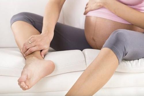 Беременная осматривает ноги