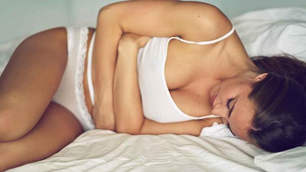 Женщина лежит, держась за живот